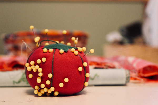 Red pin cushion with yellow pins