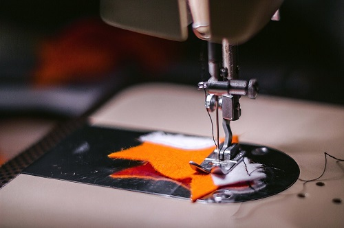 sewing with orange  piece of cloth
